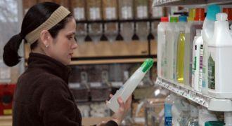 Femme lisant l'étiquette d'un produit de ménage.