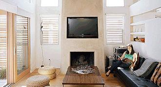 Salon slow-design avec meubles en bois et en rotin.
