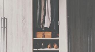 Porte de placard ouverte sur des vêtements.