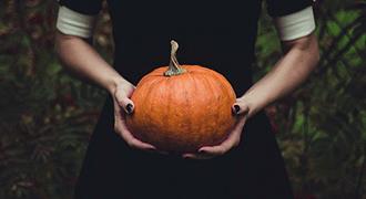 Femme aux ongles peints en noir, une citrouille entre les mains.
