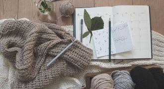 Agenda, stylo, laine et pull posés sur une table
