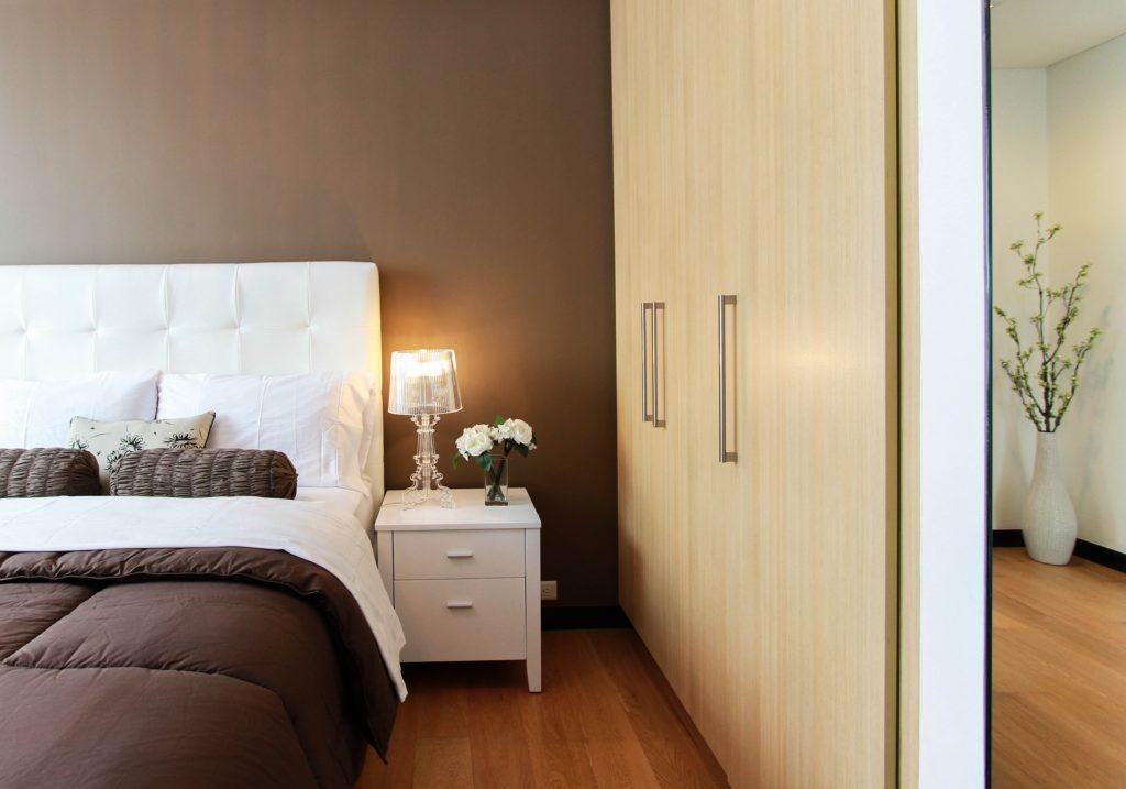 Une chambre cosy avec un lit, une table de nuit et une armoire.