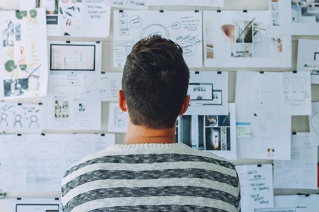 Homme de dos devant un mur de papiers, en train de choisir la configuration de son placard.