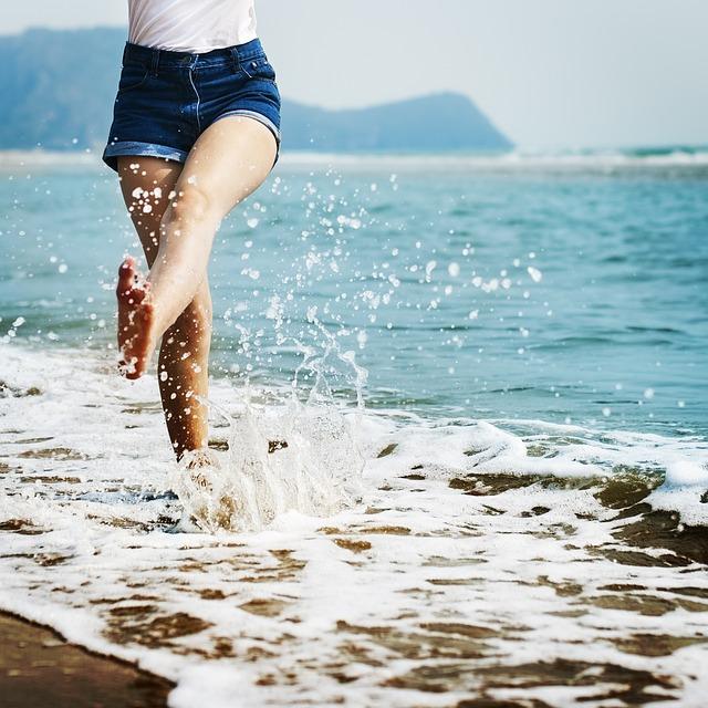 Jeune femme les pieds dans l'eau à la plage, en tenue d'été.