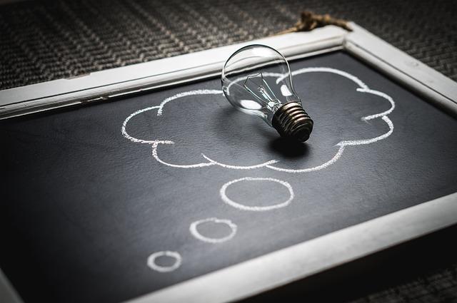 Ampoule posée sur une ardoise au milieu d'un dessin d'une bulle de pensée.